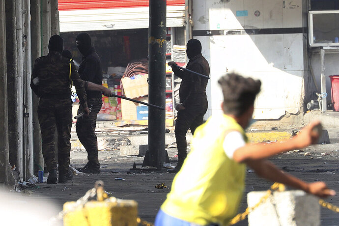 An anti-government protester prepares to throw a stone at security forces during ongoing protests in central Baghdad, Iraq, Saturday, Nov. 9, 2019. (AP Photo/Hadi Mizban)