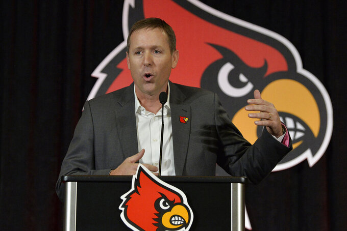 FILE - In this Dec. 4, 2018, file photo, Louisville NCAA college football head coach Scott Satterfield speaks to the media in Louisville, Ky. Satterfield's first step toward rebuilding Louisville was shoring up his roster's shaky morale.  Lack of confidence was evident in the Cardinals' 2-10 collapse that led to his hiring as coach last Dec. 4.  (AP Photo/Timothy D. Easley, File)