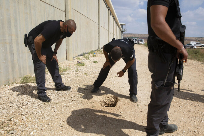 Police officers and prison guards inspect the scene of a prison escape outside the Gilboa prison in northern Israel, Monday, Sept. 6, 2021. Israeli forces on Monday launched a massive manhunt in northern Israel and the occupied West Bank after several Palestinian prisoners escaped overnight from a high-security facility in an extremely rare breakout. (AP Photo/Sebastian Scheiner)