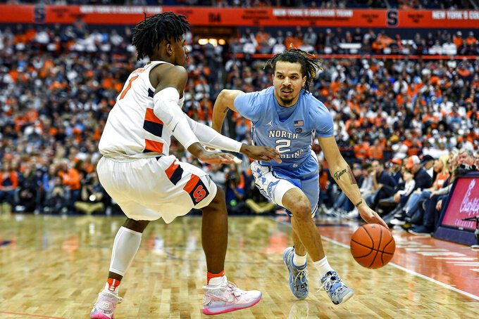 North Carolina guard Cole Anthony (2) is defended by Syracuse forward Quincy Guerrier during the first half of an NCAA college basketball game in Syracuse, N.Y., Saturday, Feb. 29, 2020. (AP Photo/Adrian Kraus)