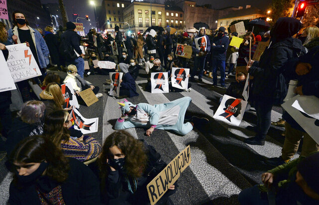 Protesters block a crossing in downtown Warsaw, Monday, Nov. 9, 2020, on the 12th straight day of anti-government protests that were triggered by the tightening of Poland's strict abortion law and are continuing despite a anti-COVID-19 ban on public gatherings. (AP Photo/Czarek Sokolowski)