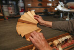 Anne Hoguet, 74, fan-maker and director of the hand fan-making museum unfolds a mounting fan in her workshop Wednesday, Jan. 20, 2021. Just like the leaves of its gilded fans, France's storied hand fan-making museum could fold up and vanish. The splendid Musee de l'Eventail in Paris, a classed historical monument, is the culture world's latest coronavirus victim. (AP Photo/Michel Euler)
