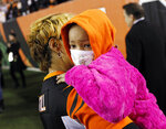 FILE - In this Thursday, Nov. 6, 2014, file photo, Leah Still is carried off the field by her grandmother following a ceremony during the first half of an NFL football game between the Cincinnati Bengals and the Cleveland Browns in Cincinnati. Leah Still planned to celebrate five years cancer-free with a dinner at her favorite steakhouse. The 10-year-old daughter of former NFL player Devon Still had to settle for a home-cooked meal when the coronavirus pandemic scuttled those plans.  Shoutouts, though, lauding her recovery from entertainment and sports stars ranging from Kevin Hart to LeBron James were a pretty sweet reward for a girl who raised cancer awareness and funds during her own fight with the disease. (AP Photo/AJ Mast, File)