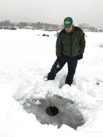 In this Feb. 23, 2019 photo, Paul Riemer of Eden Prairie, Minn., fishes through a hole in the ice of Lake Minnetonka in Wayzata, Minn. Since 1970, Minnesota's winters have been warming at a rate of more than 1 degree a decade. The change is noticeable to many who enjoy outdoor winter activities, allowing fewer opportunities for cross-country ski races, snowmobiling, dog sledding, ice fishing and outdoor skating. (AP Photo/Jeff Baenen)