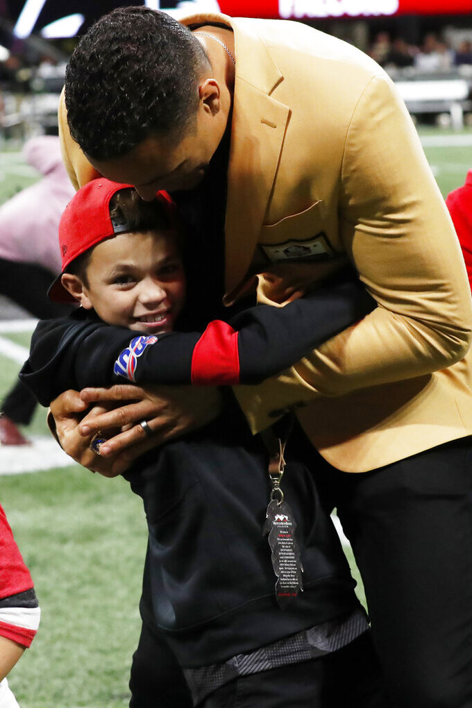 Former NFL player and Football Hall of Fame member Tony Gonzalez hold his son River Gonzalez after Tony was celebrated on the field at half time of an NFL football game between the Atlanta Falcons and the New Orleans Saints, Thursday, Nov. 28, 2019, in Atlanta. (AP Photo/John Bazemore)