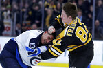 Boston Bruins center Trent Frederic (82) fights Winnipeg Jets left wing Brandon Tanev (13) during the second period of an NHL hockey game in Boston, Tuesday, Jan. 29, 2019. (AP Photo/Charles Krupa)