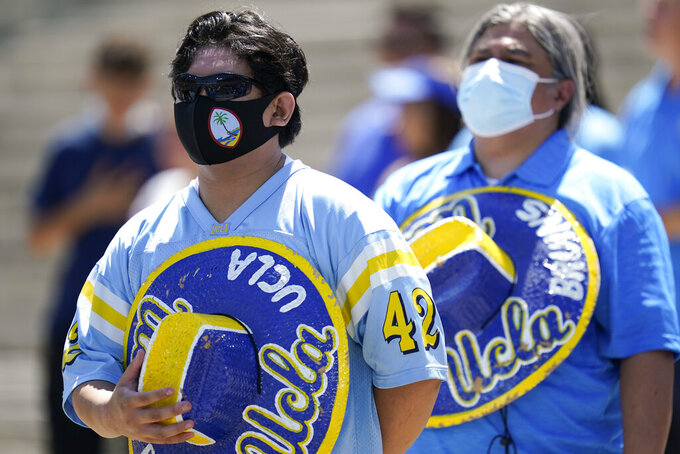 Fans wearing face masks stand as the national anthem plays before an NCAA college football game between Hawaii and UCLA, Saturday, Aug. 28, 2021, in Pasadena, Calif. College football fans headed back into stadiums Saturday, some of them for the first time in two years. (AP Photo/Ashley Landis)
