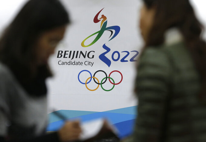 In this Nov. 4, 2014, file photo, journalists chat near the Beijing's bid for the 2022 Winter Olympics logo after attending a media briefing at the Beijing Olympics Headquarters in Beijing, China. A coalition of human-rights groups has met with the International Olympic Committee over calls to pull the 2022 Winter Olympics out of Beijing. (AP Photo/Andy Wong, File)