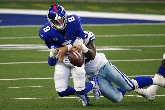 New York Giants quarterback Daniel Jones (8) fumbles the ball as he's sacked by Dallas Cowboys defensive end DeMarcus Lawrence (90) in the first half of an NFL football game in Arlington, Texas, Sunday, Oct. 11, 2020. (AP Photo/Michael Ainsworth)