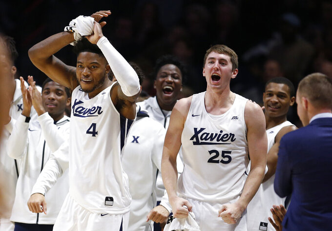 Xavier forwards Tyrique Jones (4) and Jason Carter (25) cheer their team against Missouri State during the second half of an NCAA college basketball game, Friday, Nov. 15, 2019, in Cincinnati. (AP Photo/Gary Landers)