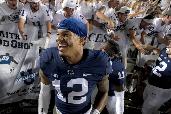 Penn State linebacker Brandon Smith (12) celebrates with fans following the 28-20 victory over Auburn after an NCAA college football game in State College, Pa., on Saturday, Sept. 18, 2021. (AP Photo/Barry Reeger)