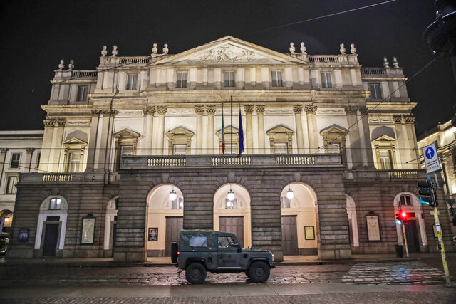 "FILE - In this early Sunday, Oct. 25, 2020 file photo, A military vehicle drives past La Scala opera theater in Milan, northern Italy. The number of performers at Milan's famed La Scala opera house positive with the coronavirus has risen to 21, even as the theater was forced to close due to new government restrictions aimed at curbing the virus' resurgence. La Scala spokesman Paolo Besana confirmed Tuesday that 18 members of the world-class chorus and  three woodwind players in the orchestra have the virus. That comes after two singers, including tenor Francesco Meli, tested positive, ahead of planned concert performances last week of ""Aida.''(AP Photo/Luca Bruno, File)"