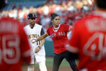 The late Los Angeles Angels pitcher Tyler Skaggs' mother, Debbie Hetman, center in red, throws the game's ceremonial first pitch, at a baseball game between the Angels and the Seattle Mariners on Friday, July 12, 2019, in Anaheim, Calif. (AP Photo/Marcio Jose Sanchez)