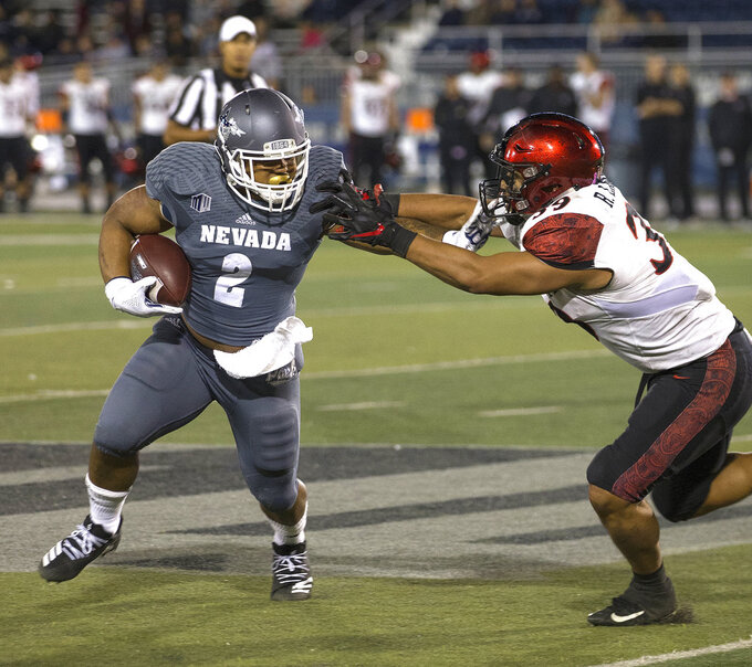 Nevada running back (2) straight-arms San Diego State's Ronley Lakalaka (39) in the second half of an NCAA college football game in Reno, Nev., Saturday, Oct. 27, 2018. (AP Photo/Tom R. Smedes)