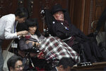 Lawmakers in wheelchairs, Eiko Kimura, left, and Yasuhiko Funago, right, of the opposition party Reiwa Shinsengumi, attend the opening of an extraordinary session at the upper house of parliament in Tokyo Friday, Oct. 4, 2019. (AP Photo/Eugene Hoshiko)