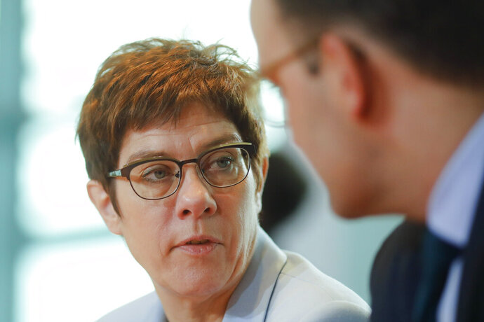 Defense Minister and chairwomen of the German Christian Democratic party (CDU),  Annegret Kramp-Karrenbauer, left, and German Health Minister Jens Spahn, right, talk as they arrive for the weekly cabinet meeting at the chancellery in Berlin, Germany, Wednesday, Nov. 13, 2019. (AP Photo/Markus Schreiber)