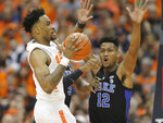 Syracuse's Oshea Brissett, left, passes under pressure from Duke's Javin Delaurier, right, during the first half of an NCAA college basketball game in Syracuse, N.Y., Saturday, Feb. 23, 2019. (AP Photo/Nick Lisi)