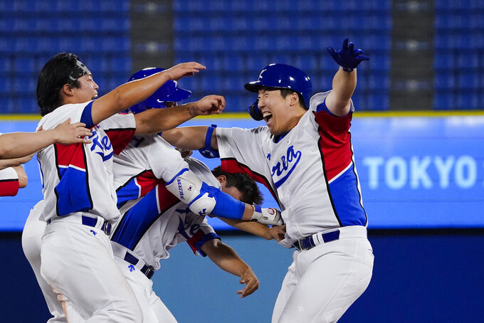 South Korea's Hyunsoo Kim, right, celebrates with teammates his game winning RBI in the ninth inning of a baseball game against the Dominican Republic at the 2020 Summer Olympics, Sunday, Aug. 1, 2021, in Yokohama, Japan. South Korea won 4-3. (AP Photo/Sue Ogrocki)