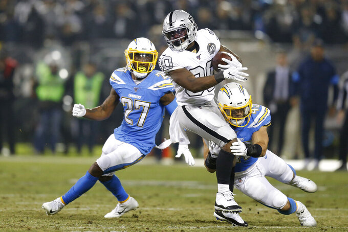 Oakland Raiders running back Jalen Richard (30) runs as Los Angeles Chargers defensive back Jaylen Watkins (27) and linebacker Drue Tranquill defend during the second half of an NFL football game in Oakland, Calif., Thursday, Nov. 7, 2019. (AP Photo/D. Ross Cameron)