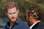 FILE - In this Friday, March 6, 2020 file photo, Britain's Prince Harry, the Duke of Sussex, and Formula One world champion Lewis Hamilton, right, chat  in Towcester, England. The BBC, seen as a respected source of news and information around the world, is facing questions about its integrity at home after a scathing report on its explosive 1995 interview with Princess Diana. Princes William and Harry, Diana's sons, late Thursday, May 20, 2021 excoriated the BBC, saying there was a direct link between the interview and their mother's death in a traffic accident two years later as she and a companion were being pursued by paparazzi. (AP Photo/Frank Augstein, file)