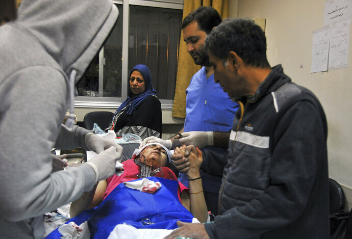 In this photo released by the Syrian official news agency SANA, a paramedic treats an injured woman wounded by Israeli missile strikes at a hospital in Damascus, Syria, Wednesday, Nov. 20, 2019. The Israeli military on Wednesday said it struck dozens of Iranian targets in Syria, carrying out a