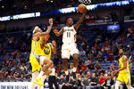 New Orleans Pelicans guard Jrue Holiday (11) shoots in front of Golden State Warriors center Willie Cauley-Stein (2) in the second half of an NBA basketball game in New Orleans, Sunday, Nov. 17, 2019. The Pelicans won 108-100. (AP Photo/Tyler Kaufman)