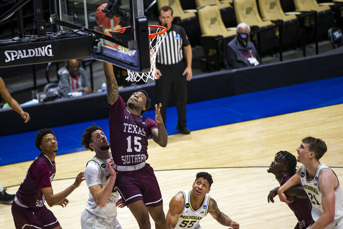 Texas Southern's Justin Hopkins (15) goes up for a shot between Michigan's Brandon Johns Jr., second from left, and Eli Brooks (55) during the second half of a first-round game in the NCAA men's college basketball tournament, Saturday, March 20, 2021, at Mackey Arena in West Lafayette, Ind. (AP Photo/Robert Franklin)