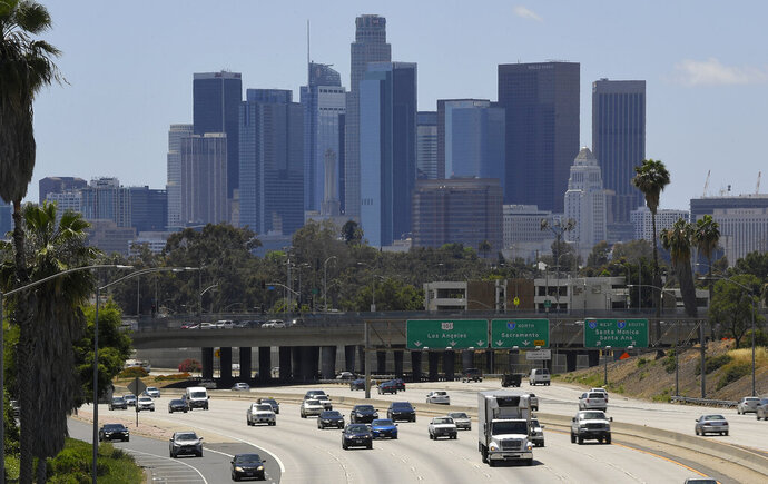 FILE - In this May 19, 2020 file photo traffic moves along Interstate 10 as downtown Los Angeles is seen in the background in Los Angeles. California voters on the November ballot will decide whether to raise property taxes on commercial and industrial land to raise up to an estimated $12 billion annually for public schools and city halls across the state. (AP Photo/Mark J. Terrill,File)