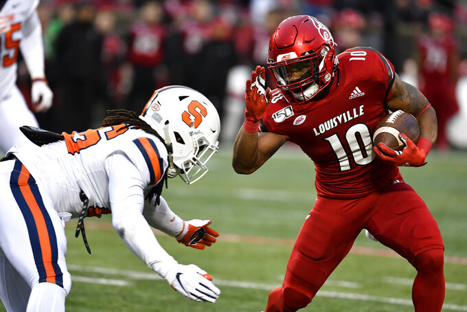 Louisville running back Javian Hawkins (10) tries to avoid a tackle by Syracuse linebacker Lakiem Williams (46) during the first half of an NCAA college football game in Louisville, Ky., Saturday, Nov. 23, 2019. (AP Photo/Timothy D. Easley)