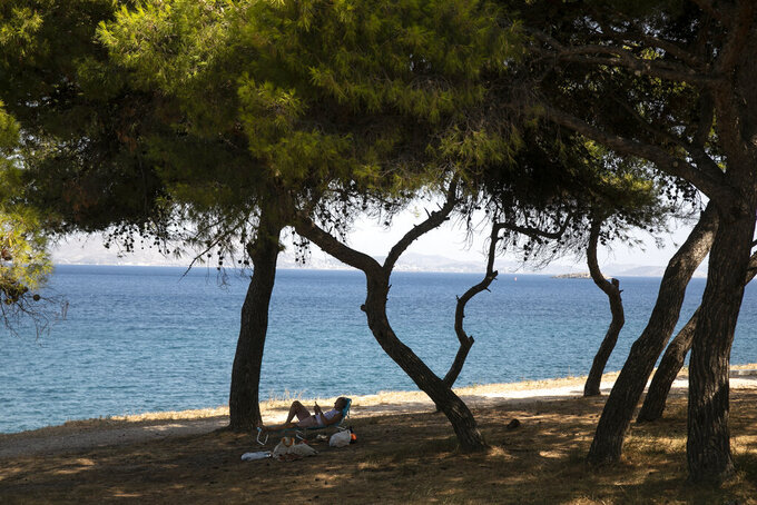 A man reads a book as he lies on a sun bed under pines at Varkiza village, a few miles southwest of Athens, on Thursday, July 29, 2021. One of the most severe heat waves recorded since 1980s scorched southeast Europe on Thursday, sending residents flocking to the coast, public fountains and air-conditioned locations to find some relief, with temperatures rose above 40 C (104 F) in parts of Greece and across much of the region. (AP Photo/Yorgos Karahalis)