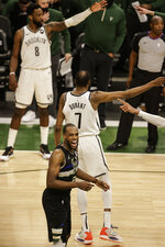 Milwaukee Bucks' Khris Middleton, foreground, reacts during the second half of Game 6 of a second-round NBA basketball playoff series  against the Brooklyn Nets, Thursday, June 17, 2021, in Milwaukee. (AP Photo/Jeffrey Phelps)