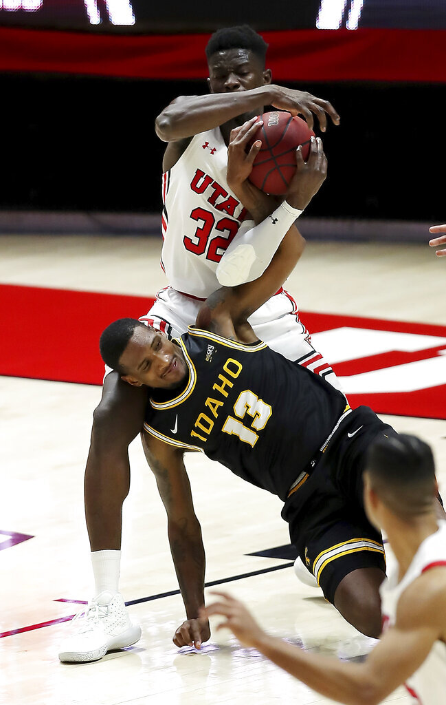 Utah center Lahat Thioune (32) battles Idaho guard DeAndre Robinson (13) for the ball during an NCAA college basketball game in Salt Lake City, Friday, Dec. 18, 2020. (Scott G Winterton/The Deseret News via AP)