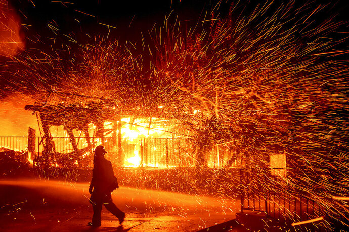A firefighter passes a burning home as the Hillside fire burns in San Bernardino, Calif., Oct. 31, 2019. (AP Photo/Noah Berger)