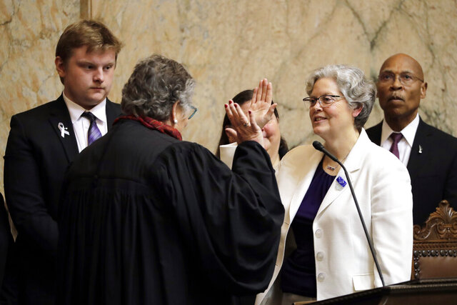 House Speaker Laurie Jinkins, D-Tacoma, second from right, is sworn in by former Washington Supreme Court Chief Justice Mary Fairhurst, second from left, Monday, Jan. 13, 2020, on the first day of the 2020 session of the Washington legislature at the Capitol in Olympia, Wash. (AP Photo/Ted S. Warren)