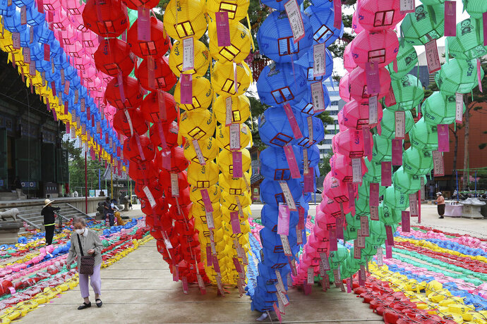 A woman wearing a face mask to help curb the spread of the coronavirus passes by lantern decorations for Buddha's birthday at the Chogyesa temple in Seoul, Monday, June 29, 2020. This year a ceremony to celebrate the birthday was put off from April 30 to May 30 due to the coronavirus. (AP Photo/Ahn Young-joon)