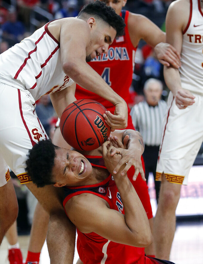 Southern California's Bennie Boatwright, top, and Arizona's Ira Lee scramble for the ball during the second half of an NCAA college basketball game in the first round of the Pac-12 men's tournament Wednesday, March 13, 2019, in Las Vegas. (AP Photo/John Locher)