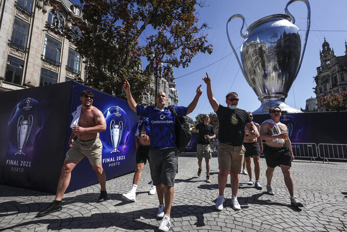 Chelsea supporters walk past a giant replica of the Champions League trophy in downtown Porto, Portugal, Friday, May 28, 2021. English clubs Manchester City and Chelsea will play the Champions League soccer final in Porto on Saturday. (AP Photo/Luis Vieira)