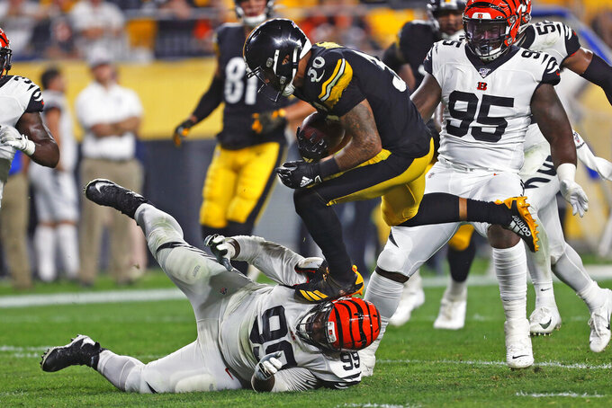 Pittsburgh Steelers running back James Conner (30) runs over Cincinnati Bengals defensive tackle Andrew Billings (99) during the second half of an NFL football game in Pittsburgh, Monday, Sept. 30, 2019. (AP Photo/Tom Puskar)