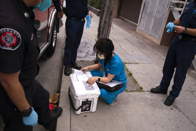 Pharmacist Stella Kim checks the temperature of a cooler containing the Pfizer COVID-19 vaccine as she and Torrance firefighters arrive at an apartment building to inoculate two sisters who have muscular dystrophy, Wednesday, May 12, 2021, in Torrance, Calif. (AP Photo/Jae C. Hong)