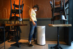 Mama Fox owner Samantha DiStefano looks at an air purifier she'll need when she opens the indoor portion of her restaurant and bar to patrons, Tuesday, Sept. 29, 2020, in New York, as she continues preparation for indoor dining. DiStefano doesn't plan on opening Wednesday, when indoor dining will be permitted in New York for the first time since March, but said she may try serving patrons at tables near the restaurant's floor-to-ceiling windows where diners can have fresh air while eating. (AP Photo/Kathy Willens)