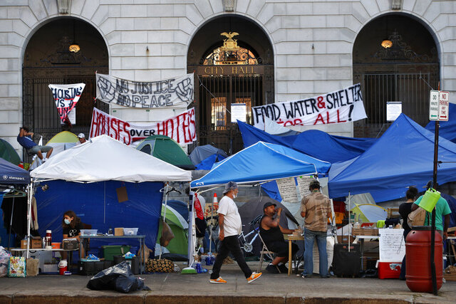 Protesters demanding attention to the needs of the homeless continue to camp in front of City Hall, Monday, Aug. 3, 2020, in Portland, Maine. City officials are trying to devise a strategy on how to handle the encampment, which began almost two weeks ago. (AP Photo/Robert F. Bukaty)