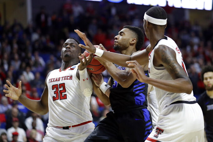 Buffalo's Jayvon Graves, center, heads to the basket as Texas Tech's Norense Odiase (32) and Tariq Owens defend during the second half of a second round men's college basketball game in the NCAA Tournament Sunday, March 24, 2019, in Tulsa, Okla. Texas Tech won 78-58. (AP Photo/Jeff Roberson)