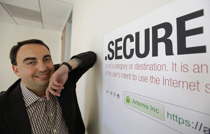 FILE - In this photo taken Friday, June 8, 2012 Alex Stamos CTO of Artemis Internet, an NCC Group Company, poses by a domain name poster at their offices in San Francisco. Stamos served as chief security officer at Facebook for three years before joining Stanford University, where he studies internet security, including systems related to conducting elections. (AP Photo/Eric Risberg, File)