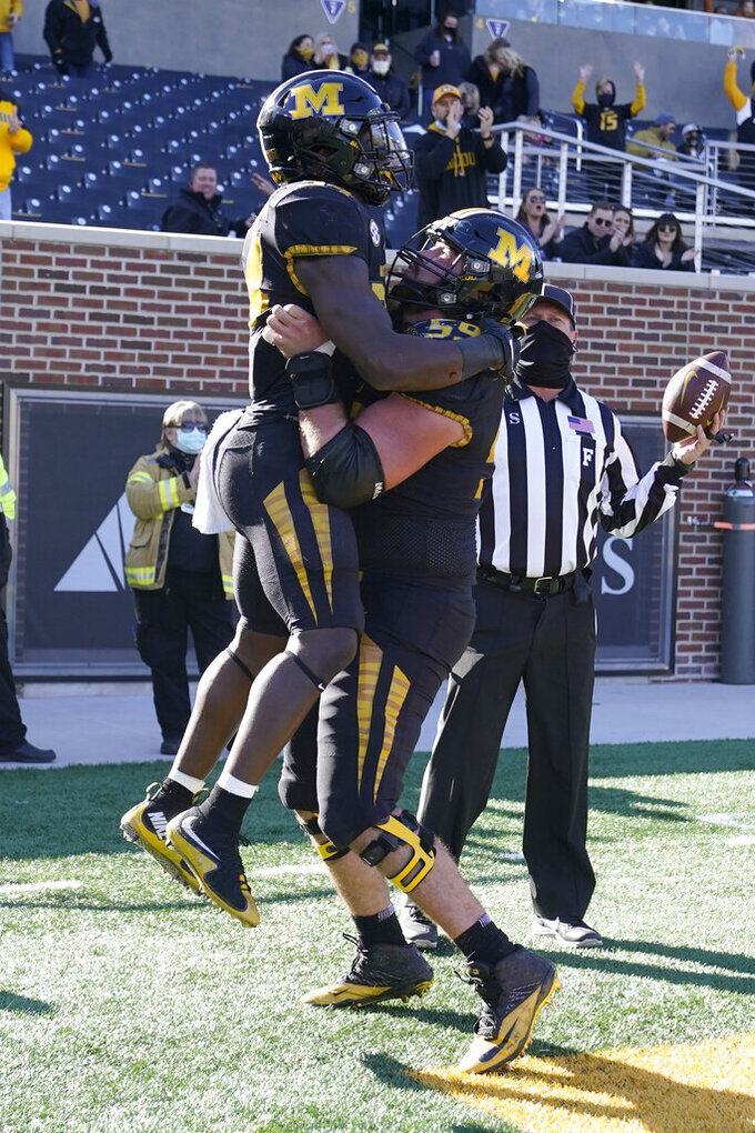 Missouri running back Larry Rountree III is congratulated by teammate Luke Griffin, right, after scoring during the first half of an NCAA college football game against Arkansas Saturday, Dec. 5, 2020, in Columbia, Mo. (AP Photo/L.G. Patterson)