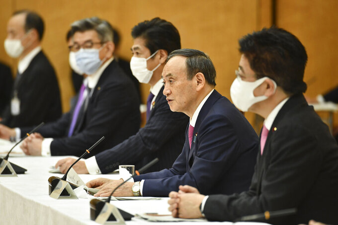 """Japanese Prime Minister Yoshihide Suga, second from right, speaks during a meeting of the coronavirus infection control headquarters at his office in Tokyo Friday, Jan. 22, 2021. Suga, in a speech earlier, said the vaccine is """"the clincher"""" in the fight against the pandemic and vowed to start vaccinations as soon as late February, when a health ministry approval of the Pfizer vaccine, the first applicant, is expected. (Kazuhiro Nogi/Pool Photo via AP)"""