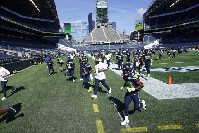 Seattle Seahawks tight ends coach Pat McPherson, center, runs to the locker room with players before an NFL football game against the Dallas Cowboys, Sunday, Sept. 27, 2020, in Seattle. (AP Photo/Elaine Thompson)
