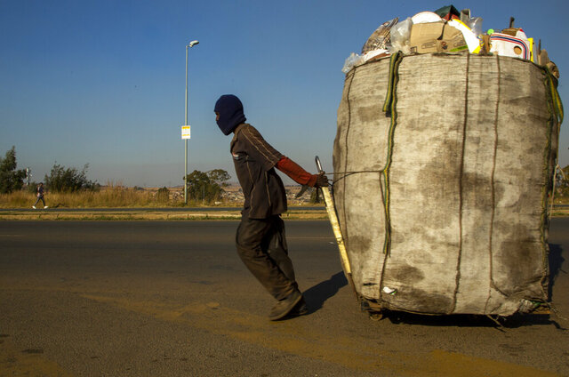 A man pulls a trolley filled with cardboard and plastic bottles for recycling through the streets at Phumlamqashi informal settlement near Johannesburg, South Africa, Wednesday, June 3, 2020. (AP Photo/Themba Hadebe)