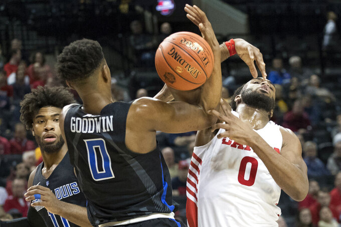 Saint Louis guard Jordan Goodwin, left, battles for the ball with Dayton forward Josh Cunningham during the first half of an NCAA college basketball game in the Atlantic 10 Conference tournament, Friday, March 15, 2019, in New York. (AP Photo/Mary Altaffer)