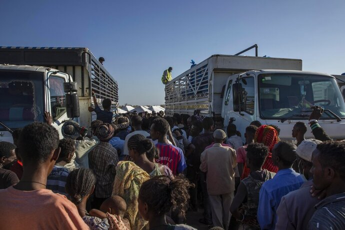 FILE - In this Tuesday, Nov. 24, 2020 file photo, Tigray refugees who fled the conflict in Ethiopia's Tigray region, wait to receive aid at Umm Rakouba refugee camp in Qadarif, eastern Sudan. A key U.N. aid agency says needs for humanitarian assistance have ballooned this year because of COVID-19, projecting that a staggering 235 million people — who together would make up the world's fifth most-populous country — are likely to require such help next year for troubles like the pandemic as well as war, forced migration and the impact of global warming (AP Photo/Nariman El-Mofty)