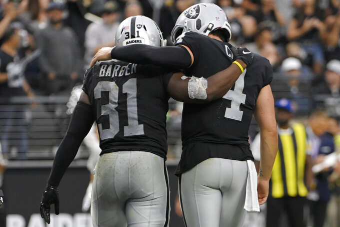 Las Vegas Raiders running back Peyton Barber (31) and quarterback Derek Carr (4) celebrate after Barber scored a touchdown against the Miami Dolphins during the second half of an NFL football game, Sunday, Sept. 26, 2021, in Las Vegas. (AP Photo/David Becker)
